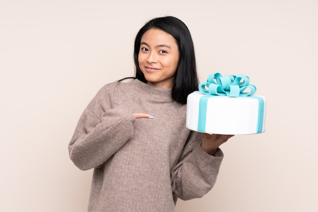 Teenager asian girl holding a big cake on beige wall with surprise facial expression