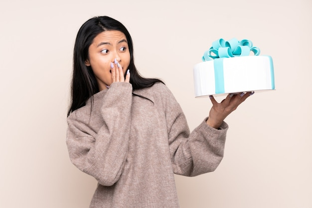 Teenager asian girl holding a big cake isolated on beige with surprise and shocked facial expression
