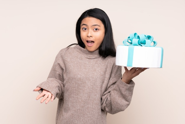 Teenager asian girl holding a big cake isolated on beige