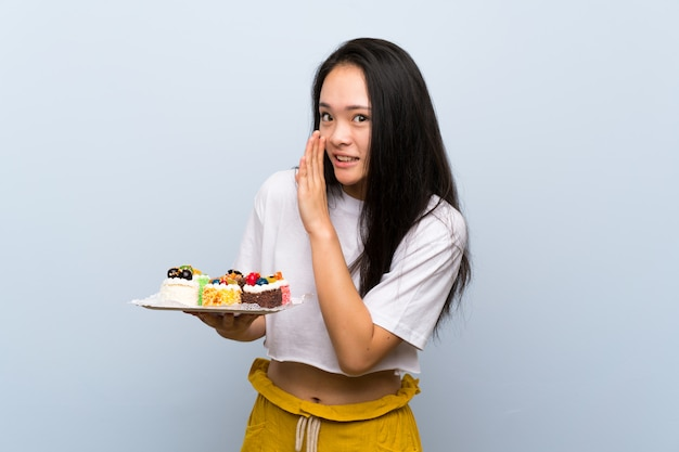 Teenager asian girl holding lots of different mini cakes whispering something