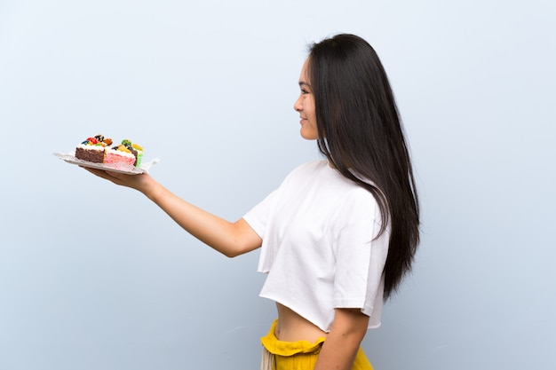 Teenager asian girl holding lots of different mini cakes with happy expression