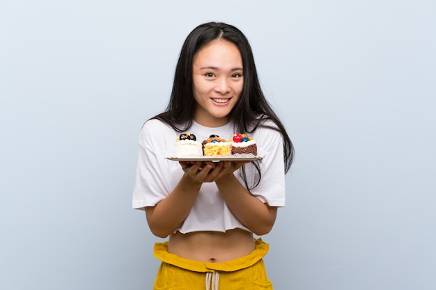 Teenager asian girl holding lots of different mini cakes