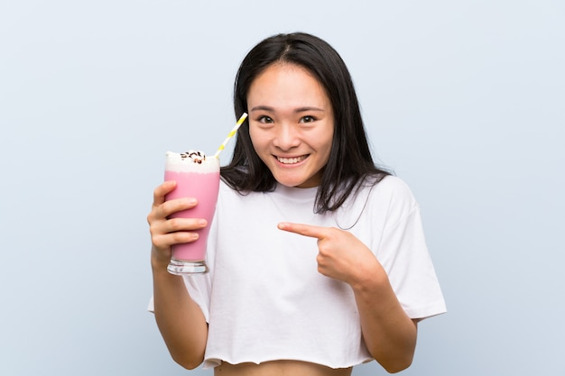 Teenager asian girl holding a strawberry milkshake with surprise facial expression