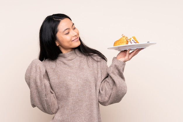 Teenager asian girl holding waffles isolated on beige