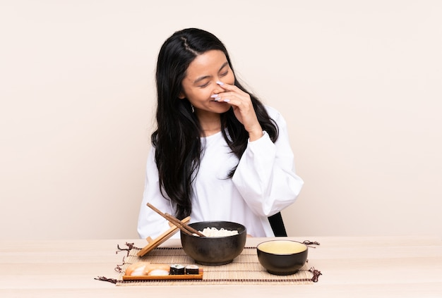 Teenager asian woman eating asian food isolated on beige background