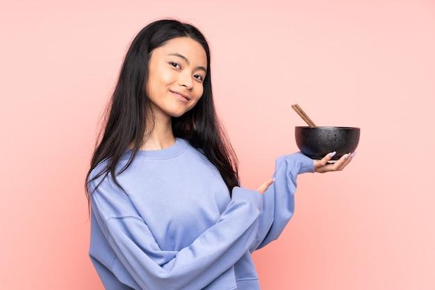 ベージュで隔離され、箸で麺のボウルを保持しながらそれを指しているティーンエイジャーのアジアの女性