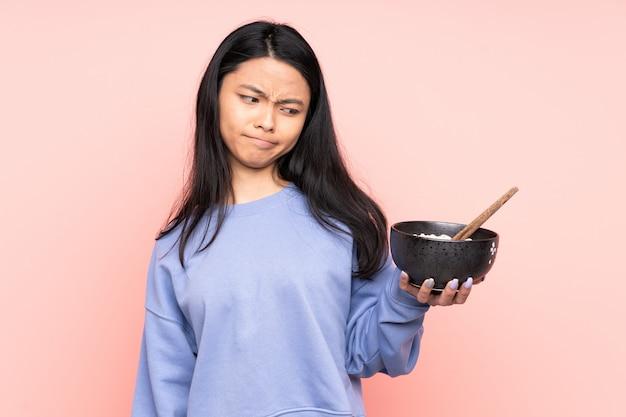 Азиатская женщина подросток, изолированных на бежевой стене с грустным выражением, держа миску лапши с палочками для еды