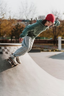 Подросток в скейтпарке веселится