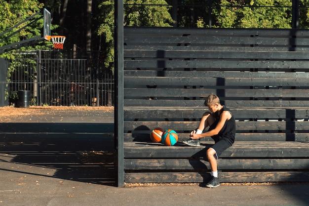 靴紐を結ぶスポーツグラウンドに座っているティーンエイジャーのバスケットボール選手