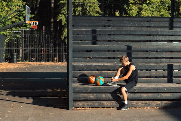 Teenager basketball player sitting at sports ground tying shoelaces