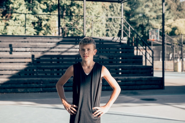 スポーツの遊び場に立っているティーンエイジャーのバスケットボール選手