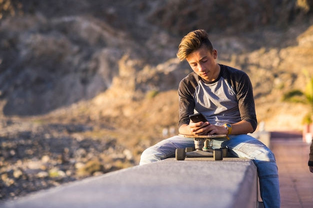 Teenager at the beach sitting on a wall using his phones with his skateboard - boy wearing jeans focused on the social or playing video games