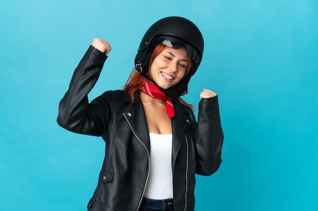 Teenager biker girl on blue celebrating a victory