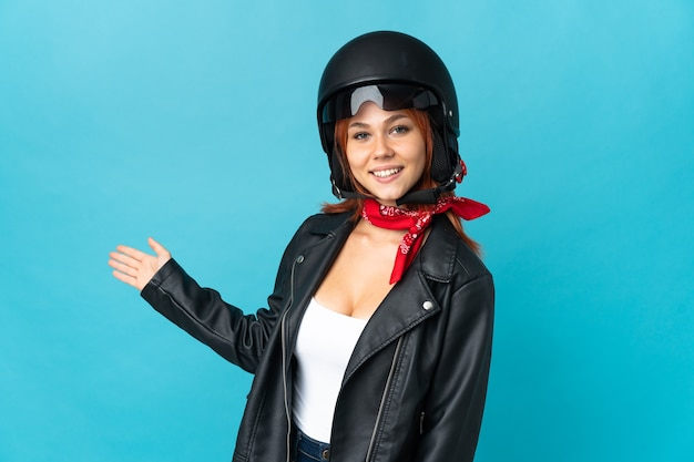 Teenager biker girl on blue extending hands to the side for inviting to come