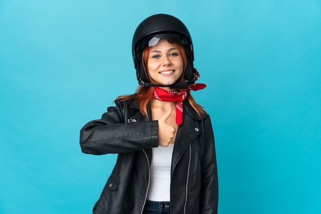 Teenager biker girl on blue giving a thumbs up gesture