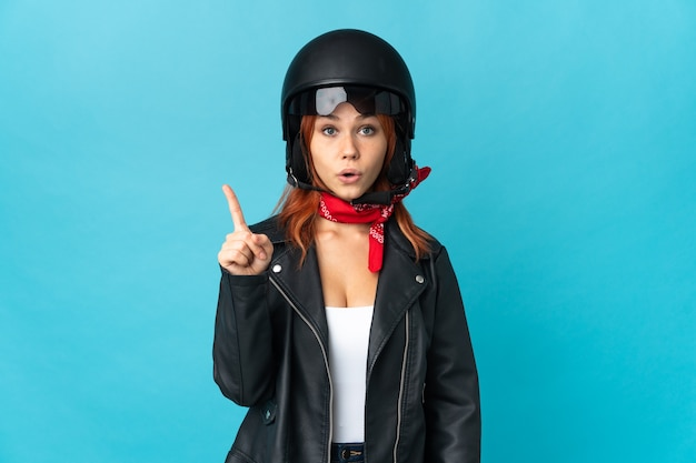 Teenager biker girl on blue intending to realizes the solution while lifting a finger up