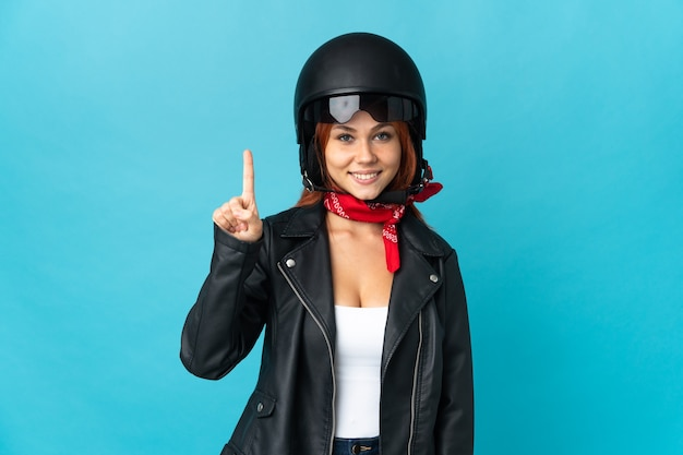 Teenager biker girl on blue showing and lifting a finger in sign of the best
