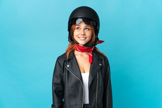 Teenager biker girl on blue thinking an idea while looking up