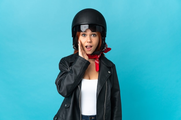 Teenager biker girl on blue with surprise and shocked facial expression