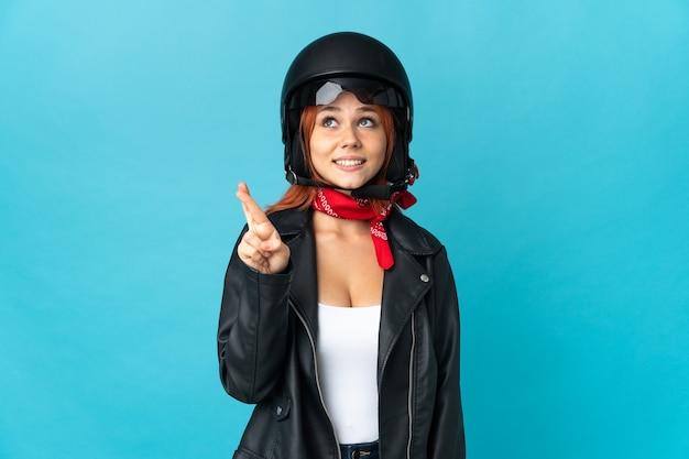 指が交差し、最高を願って青い壁に隔離されたティーンエイジャーのバイカーの女の子