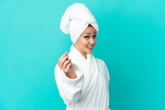 Teenager blonde girl in a bathrobe over isolated blue background making money gesture