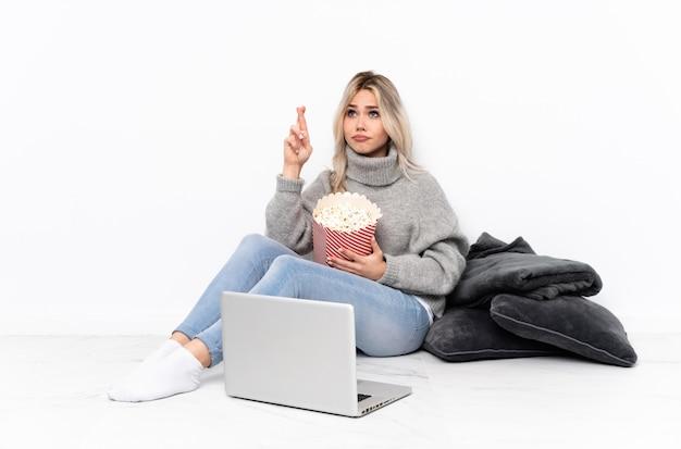 Блондинка-подросток ест попкорн во время просмотра фильма на ноутбуке, скрестив пальцы и желая лучшего