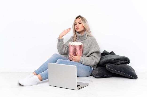 Блондинка подросток ест попкорн во время просмотра фильма на ноутбуке с усталым и больным выражением