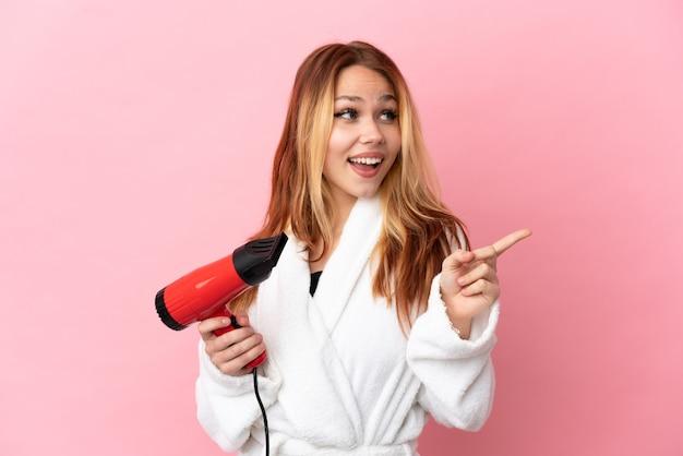 Блондинка-подросток держит фен на изолированном розовом фоне, намереваясь реализовать решение, подняв палец вверх