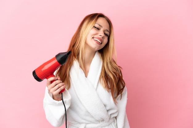 Блондинка девушка подросток держит фен на изолированном розовом фоне смеясь