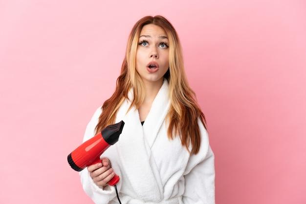 Блондинка девушка-подросток держит фен на розовом фоне, глядя вверх и с удивленным выражением лица