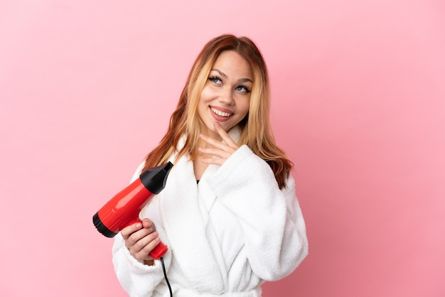 Блондинка девушка-подросток держит фен на изолированном розовом фоне, глядя вверх, улыбаясь
