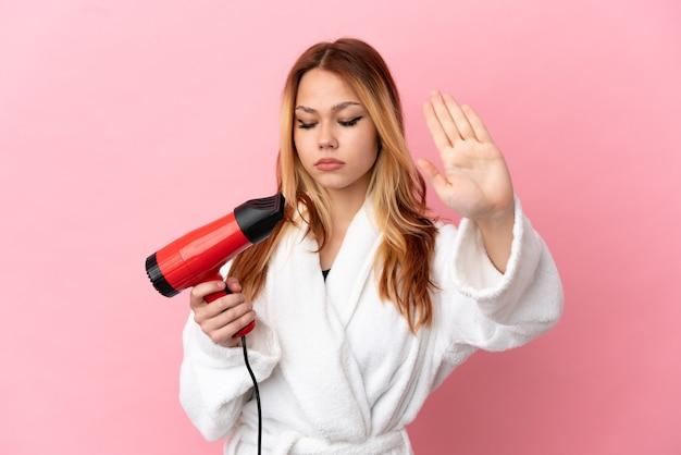 Блондинка девушка-подросток держит фен на изолированном розовом фоне, делая жест стоп и разочарована