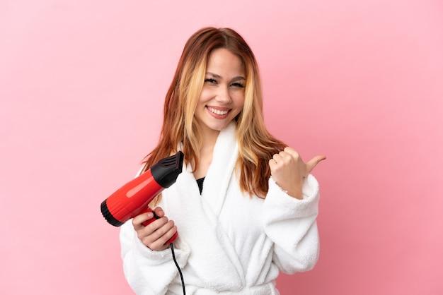 Блондинка девушка-подросток держит фен на изолированном розовом фоне, указывая в сторону, чтобы представить продукт