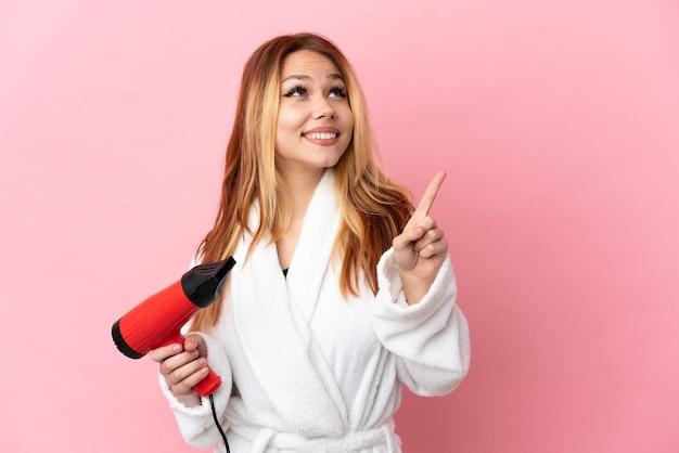 Блондинка-подросток держит фен на изолированном розовом фоне, указывая на отличную идею