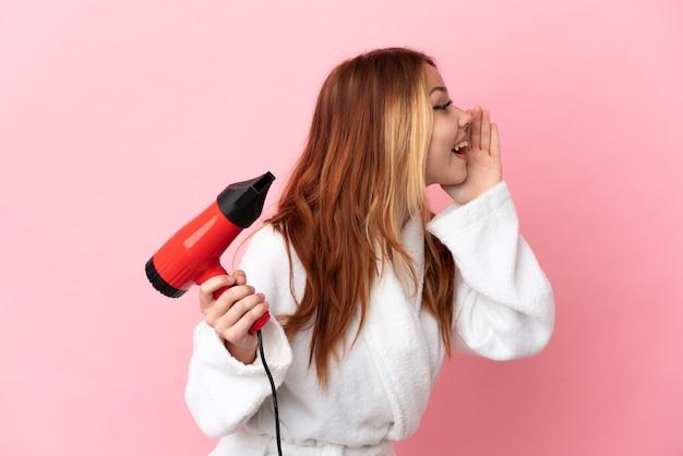 Блондинка-подросток держит фен на изолированном розовом фоне и кричит с широко открытым ртом
