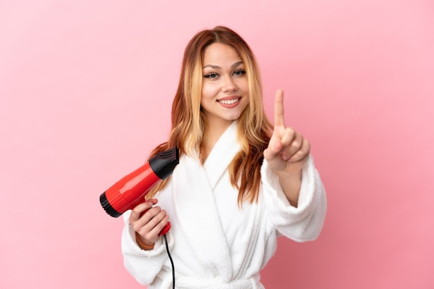 Блондинка девушка-подросток держит фен на изолированном розовом фоне, показывая и поднимая палец