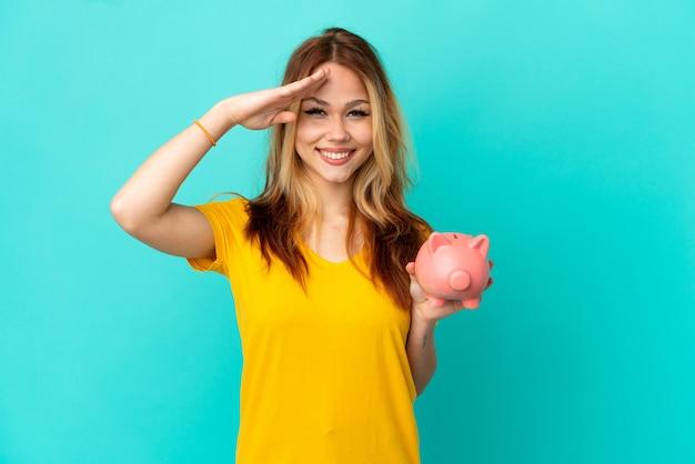 Блондинка девочка-подросток держит копилку на синем фоне, салютуя рукой с счастливым выражением лица