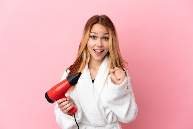 Teenager blonde girl holding a hairdryer over isolated pink background celebrating a victory in winner position