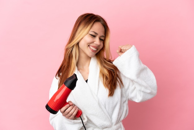 Teenager blonde girl holding a hairdryer over isolated pink background celebrating a victory
