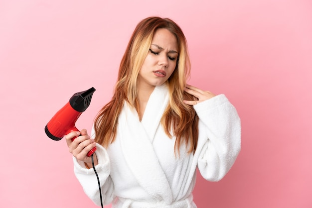 Teenager blonde girl holding a hairdryer over isolated pink background suffering from pain in shoulder for having made an effort