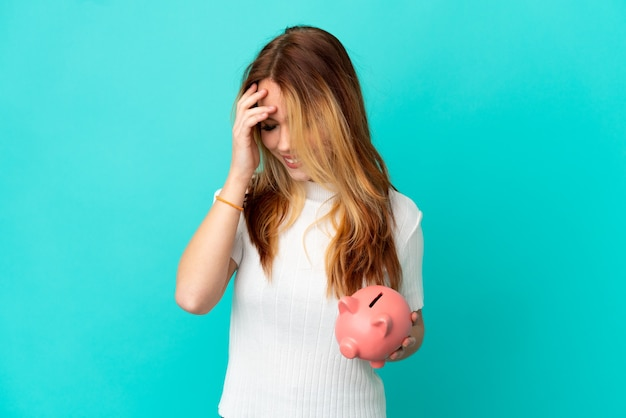 Teenager blonde girl holding a piggybank over isolated blue background laughing