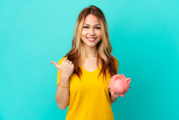 Teenager blonde girl holding a piggybank over isolated blue background pointing to the side to present a product