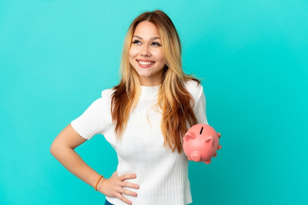 Teenager blonde girl holding a piggybank over isolated blue background posing with arms at hip and smiling
