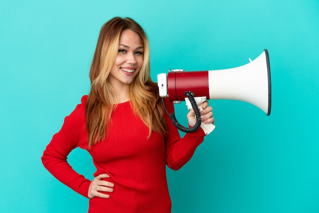 Teenager blonde girl over isolated blue background holding a megaphone and smiling