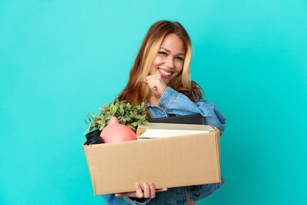 Блондинка-подросток делает движение, поднимая коробку, полную вещей, празднуя победу