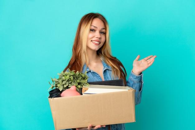 Блондинка-подросток делает движение, поднимая коробку, полную вещей, протягивая руки в сторону, приглашая прийти