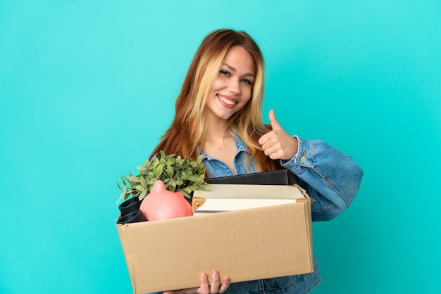 Блондинка-подросток делает движение, поднимая коробку, полную вещей, показывая большой палец вверх