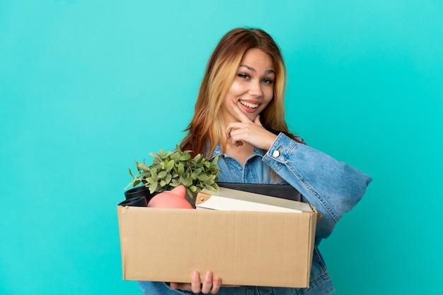 Блондинка-подросток делает движение, поднимая коробку, полную вещей, счастливую и улыбающуюся
