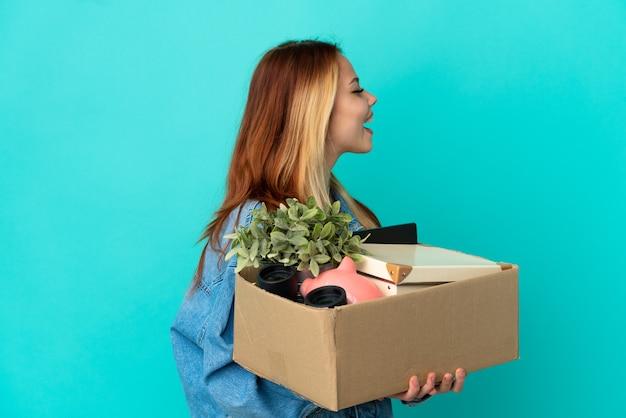 Блондинка-подросток делает движение, поднимая коробку, полную вещей, смеясь в боковом положении
