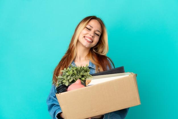Блондинка-подросток делает движение, поднимая коробку, полную вещей, смеясь